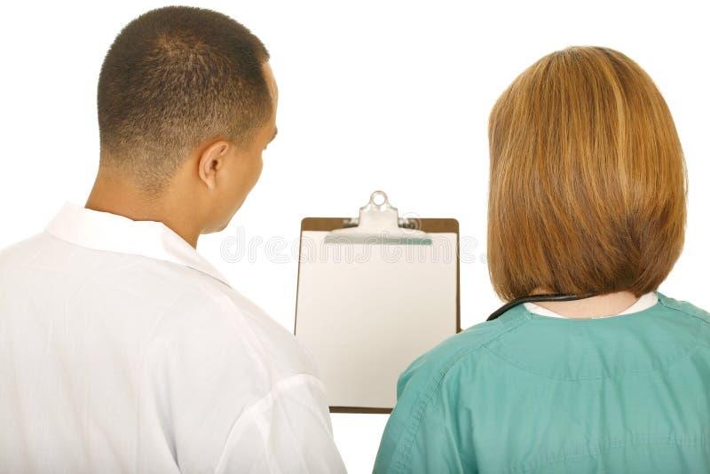 Ärzteteam, das Klipp-Vorstand betrachtet stockfoto