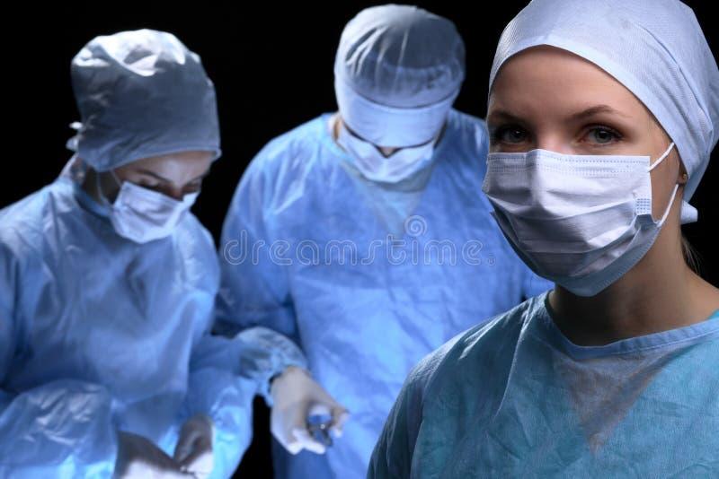 Ärzteteam, das Operation durchführt Fokus an der Ärztin stockfotografie