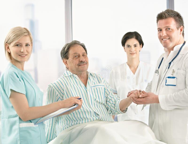 Ärzteteam, das um Patienten sich kümmert stockbilder