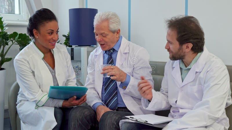 Ärzteteam von drei Doktoren sitzt auf der Couch am Krankenhaus lizenzfreies stockbild