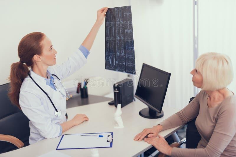 Ärztin überprüft Röntgenstrahl im Büro stockfotos