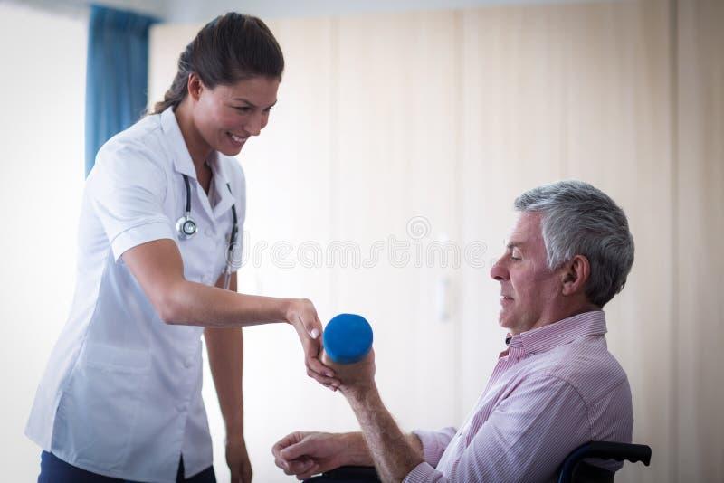 Ärztin, die älteren Mann in anhebendem Dummkopf unterstützt lizenzfreies stockbild