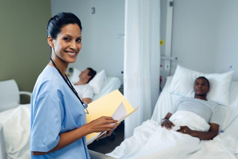 Ärztin, die ärztlichen Attest im Bezirk auf Krankenhaus betrachtet lizenzfreie stockfotografie