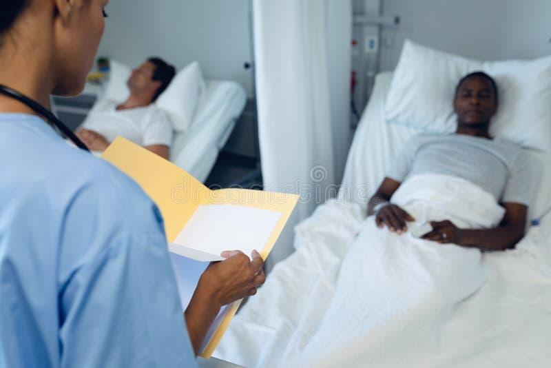 Ärztin, die ärztlichen Attest im Bezirk betrachtet stockfotografie