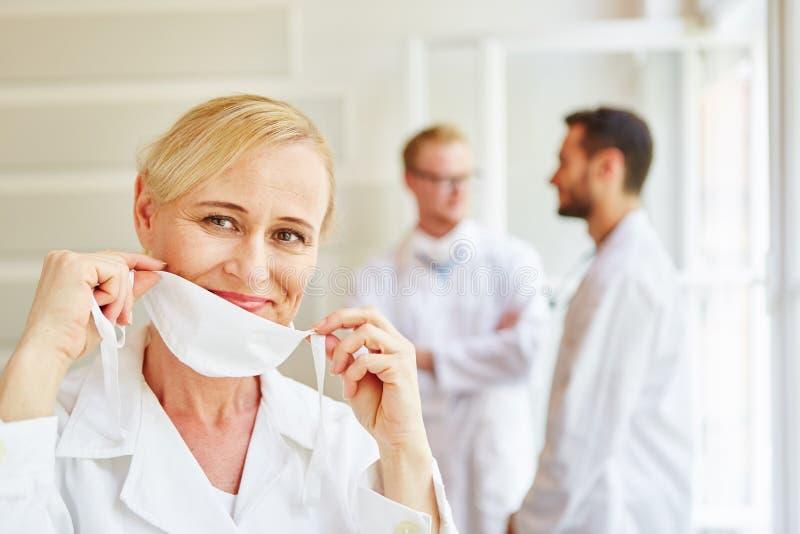 Ärztin, die an chirurgische Maske setzt stockfotografie