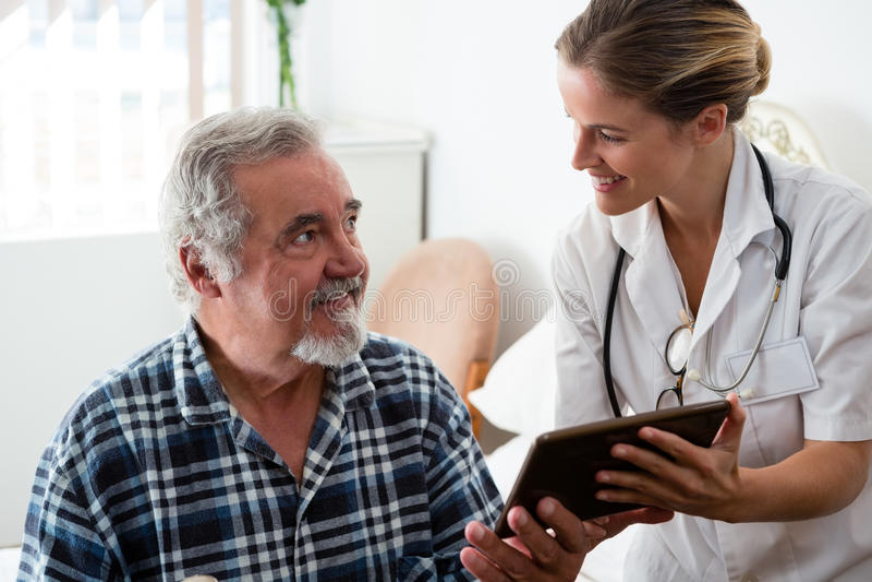 Ärztin, die dem Mann digitale Tablette im Ruhesitz zeigt stockfotografie