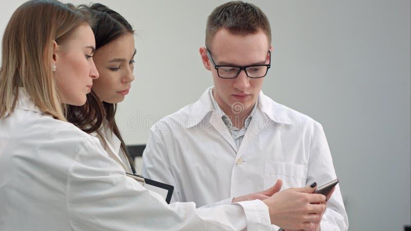Ärztin, die ihrem Ärzteteam etwas auf Tablette zeigt lizenzfreies stockbild