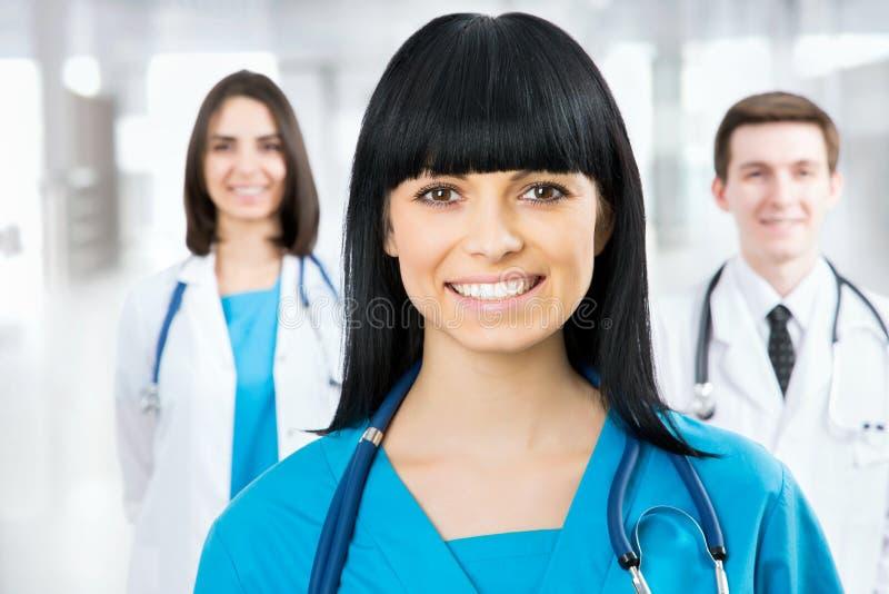 Ärztin, die im frount seines Teams steht lizenzfreies stockbild