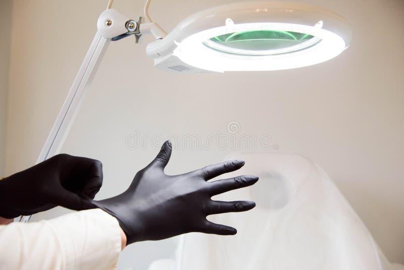 Ärztin, die Kosmetiker sterile Handschuhe trägt, bereitet vor sich, Kunden zu empfangen stockfotos