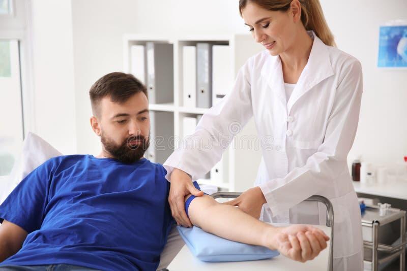 Ärztin, die männlichen Spender für Bluttransfusion im Krankenhaus vorbereitet lizenzfreie stockfotografie