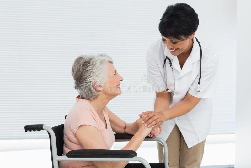 Ärztin, die mit einem älteren Patienten im Rollstuhl spricht stockfotos