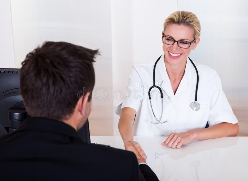 Ärztin, die mit einem Patienten sich berät stockbild