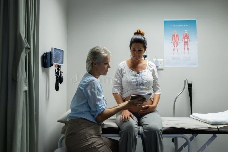 Ärztin, die mit schwangerer Frau über digitaler Tablette im Krankenhaus sich bespricht stockfoto