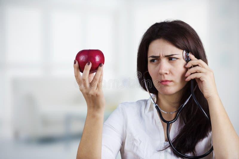 Ärztin, die roten Apfel hält lizenzfreies stockfoto