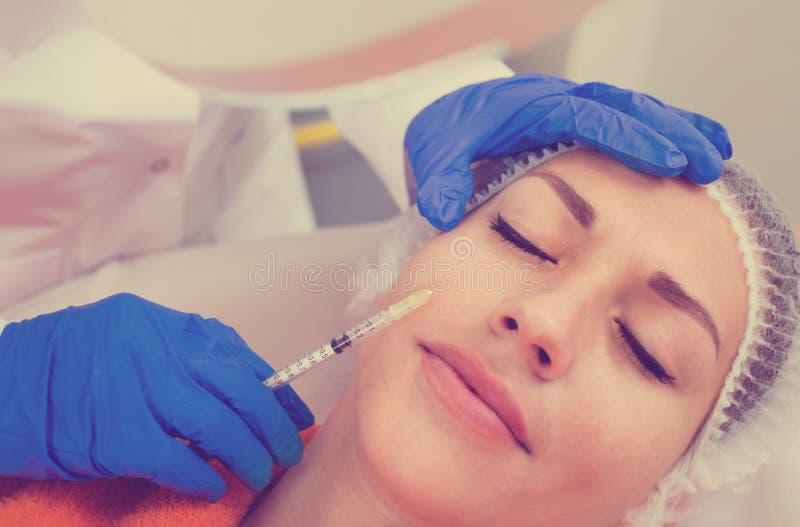 Ärztin, die Schönheitseinspritzung junge Klientin antut stockbilder