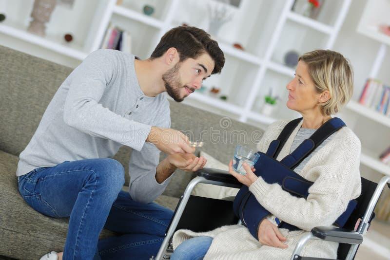 Ärztin, die zu Hause älteren Mann in anhebendem Dummkopf unterstützt lizenzfreie stockfotos