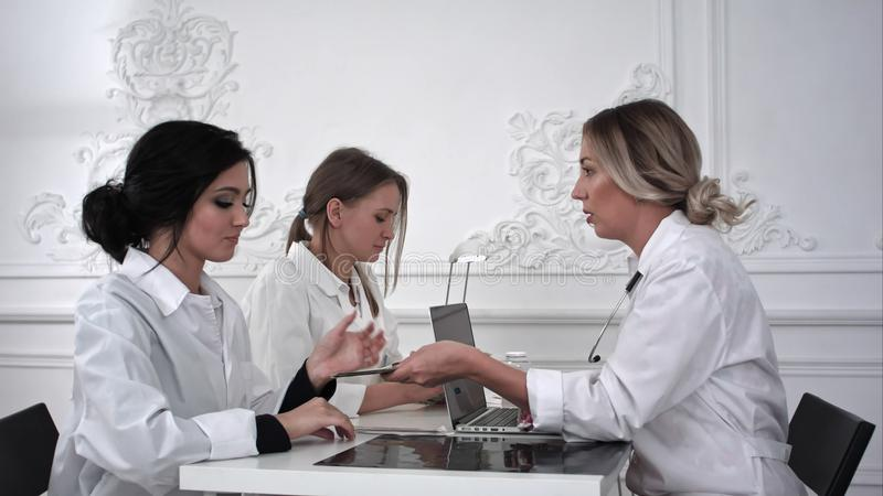 Ärztin gibt den netten Krankenschwestern im Büro das Geld stockbild