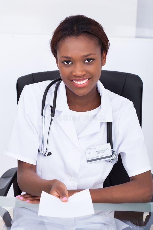 Ärztin Giving Prescription Paper am Schreibtisch stockfoto