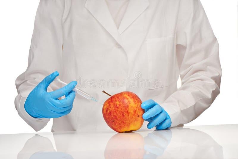 Ärztin im weißen medizinischen Kleid und in Blau entkeimten chirurgischen Handschuhen macht Einspritzung zum schönen Apfel mit Pl lizenzfreie stockfotos