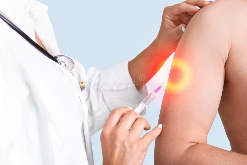 Ärztin impft Mann im Krankenhaus, benutzt Spritze und Antigift Nurce gibt Impfschuß im Arm, lokalisiert über blauem Studio stockbild