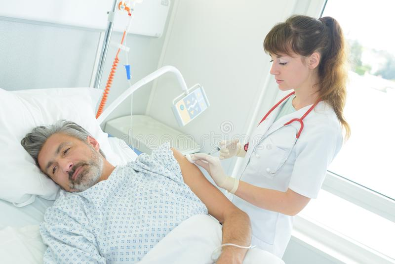 Ärztin injiziert kranken Mann im Bett lizenzfreie stockbilder