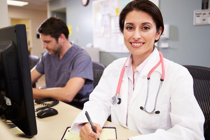 Ärztin With Male Nurse, das an der Krankenschwester-Station arbeitet lizenzfreie stockbilder