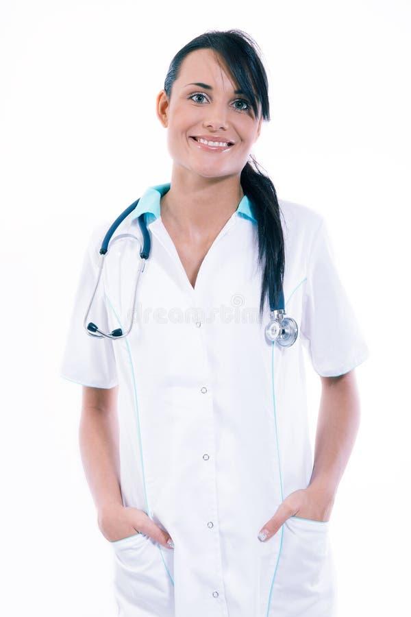 Ärztin mit dem Stethoskop, das im Büro steht und an der Kamera lächelt stockfotografie