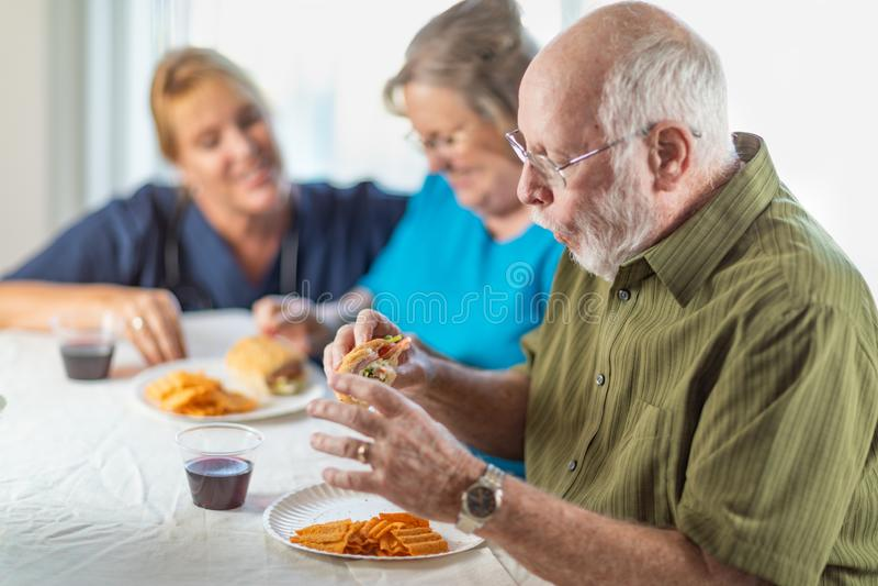 ?rztin oder Krankenschwester Serving Senior Adult verbinden Sandwiche stockfoto