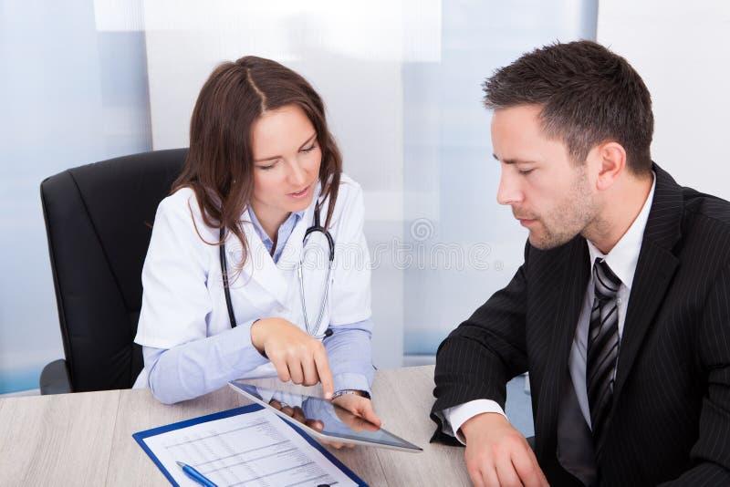 Ärztin Showing Digital Tablet lizenzfreie stockfotografie