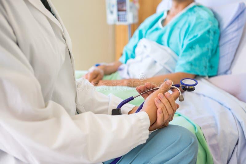 Ärztin Sitting With Patient auf Krankenhaus-Bett stockfoto