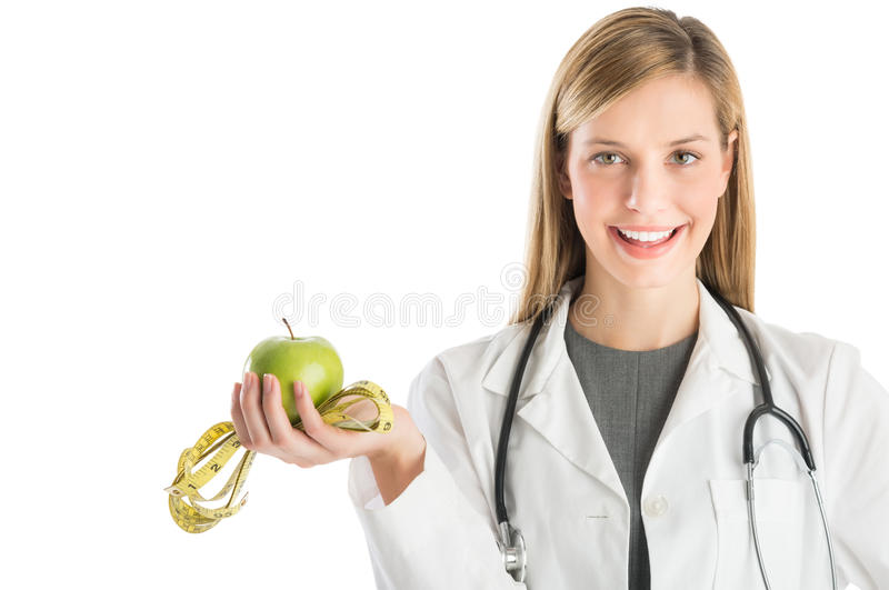 Ärztin With Stethoscope Holding Smith Apple And Tape Meas stockfoto