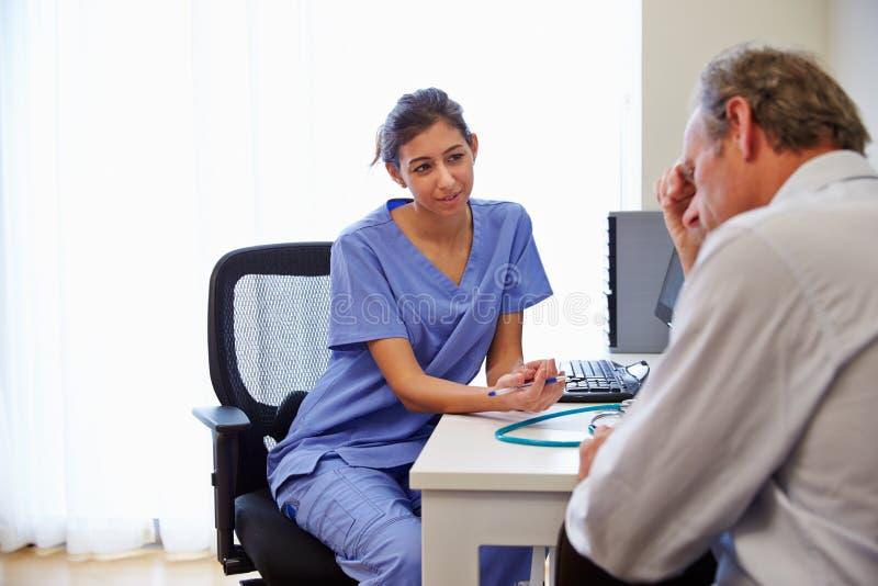 Ärztin Treating Patient Suffering mit Krise stockbild