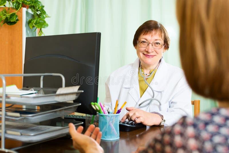 Ärztin und Patient besprechen etwas stockfotografie