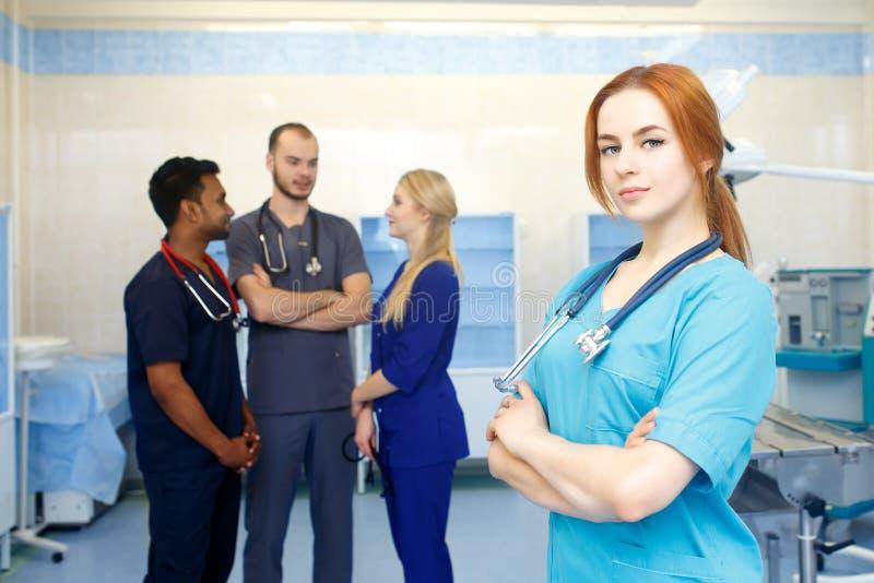 Ärztin vor dem Team, Kamera mit Ärzteteam im Hintergrund betrachtend Gemischtrassiges Team von jungen Doktoren herein lizenzfreies stockbild