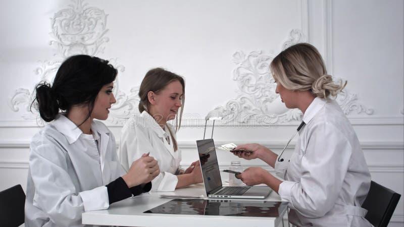 Ärztin zahlt den Krankenschwestern im Büro das Geld stockbild