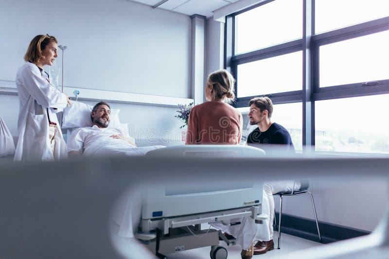Ärztinbesuchspatient im Krankenhauszimmer lizenzfreie stockfotografie