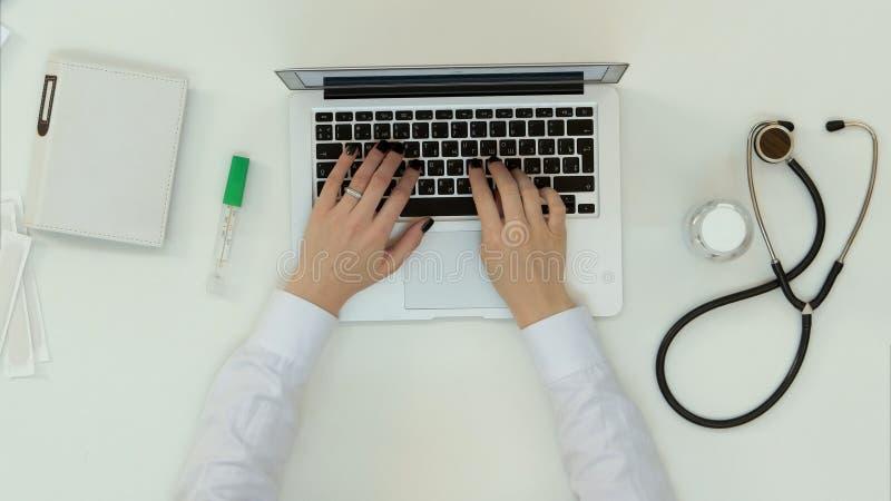 Ärztinhände, die auf Laptop schreiben stockfoto