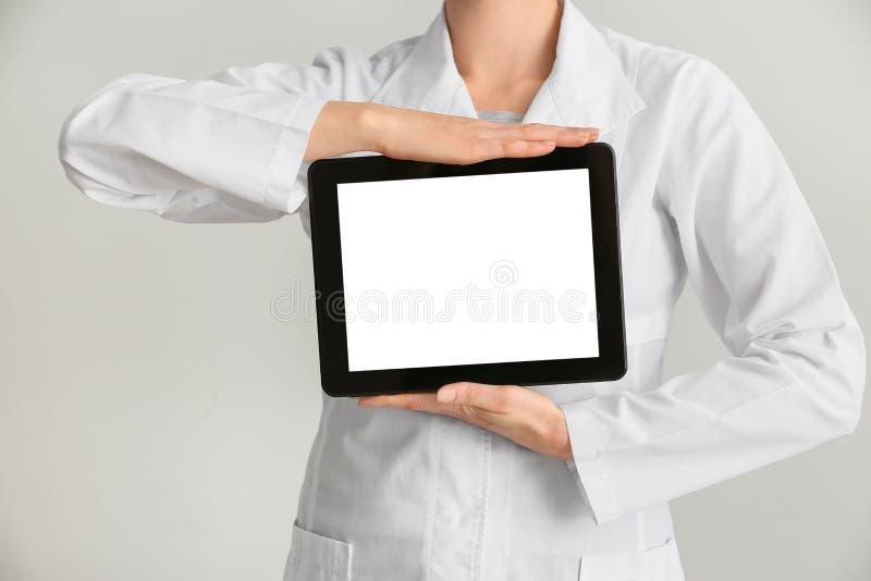 Ärztinholdingtablet-computer auf weißem Hintergrund lizenzfreie stockfotografie