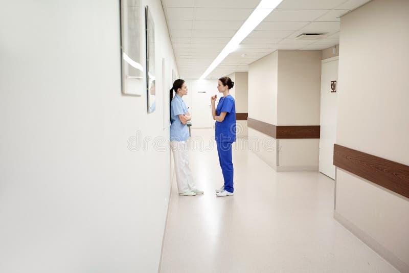 Ärztinnen oder Krankenschwestern, die am Krankenhaus sprechen lizenzfreies stockbild