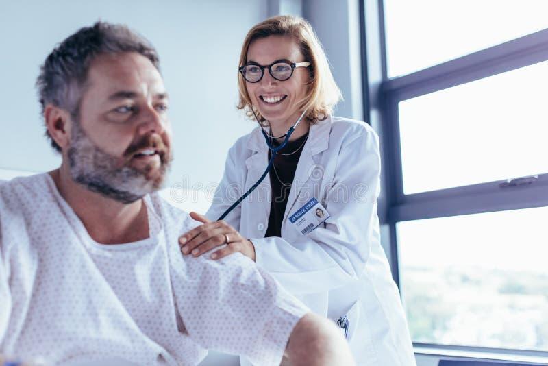 Ärztliche Untersuchung des reifen Mannes in der Krankenstation stockbild