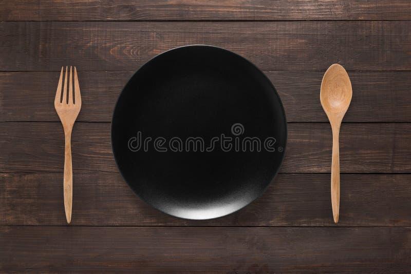 Äta begrepp Sked, gaffel och svart maträtt på träbackgroen arkivfoto