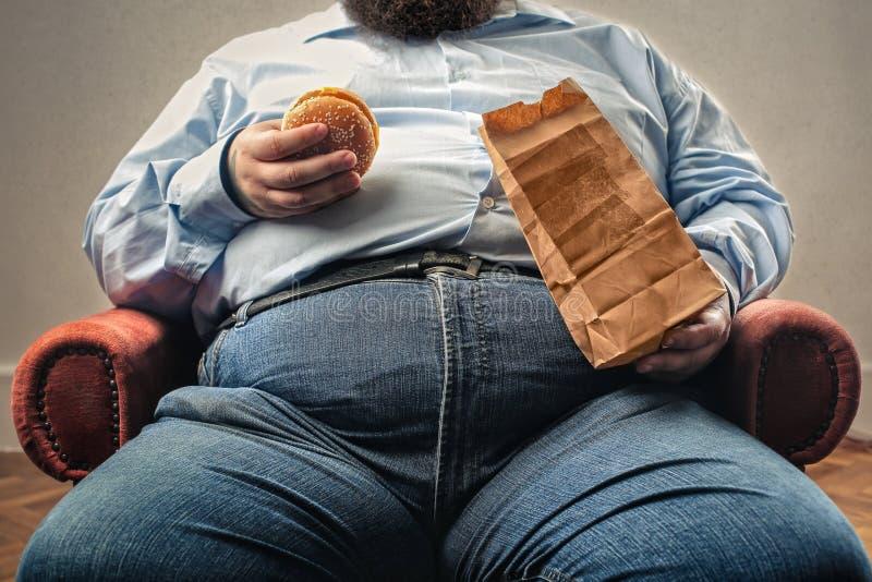 äta den feta hamburgaremannen royaltyfri bild