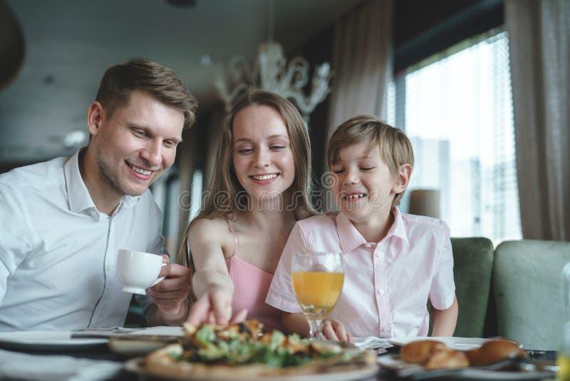 Äta den lyckliga familjen med barnet inomhus arkivfoto
