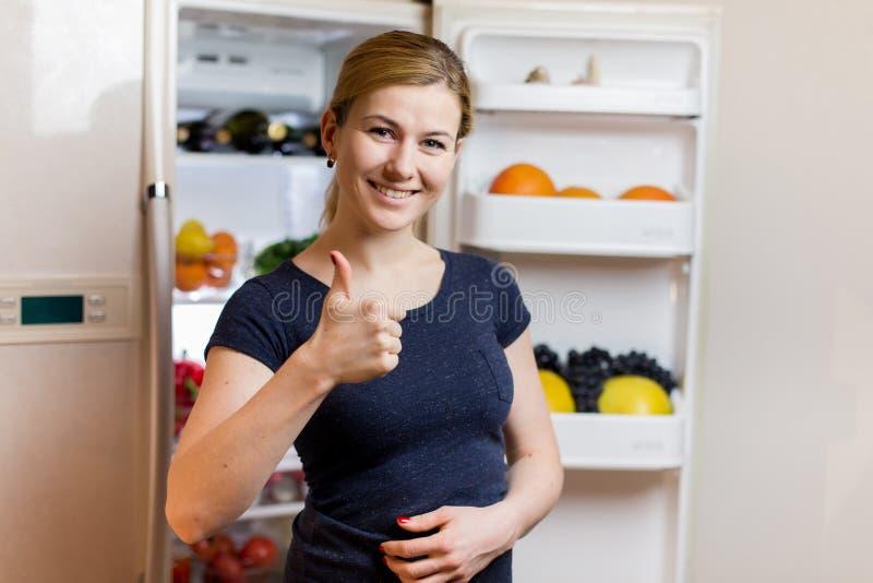 äta för begrepp som är sunt Härlig ung kvinna nära kylskåpet med sund mat bär fruktt grönsaker royaltyfri fotografi