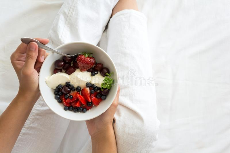 äta för begrepp som är sunt Kvinna` s räcker innehavbunken med keso med kräm, jordgubben, körsbäret, krusbäret och blåbäret arkivfoton