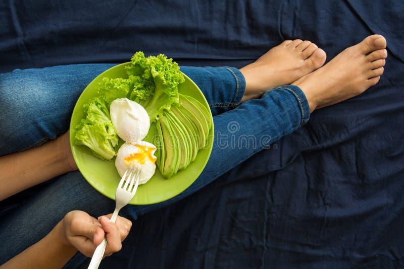 äta för begrepp som är sunt Kvinna` s räcker innehavplattan med grönsallat, avokadoskivor och tjuvjagade ägg arkivbild