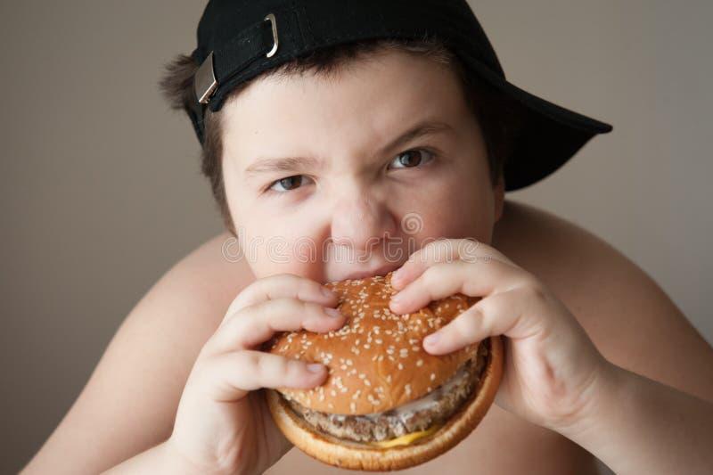 äta för pojkehamburgare arkivbild