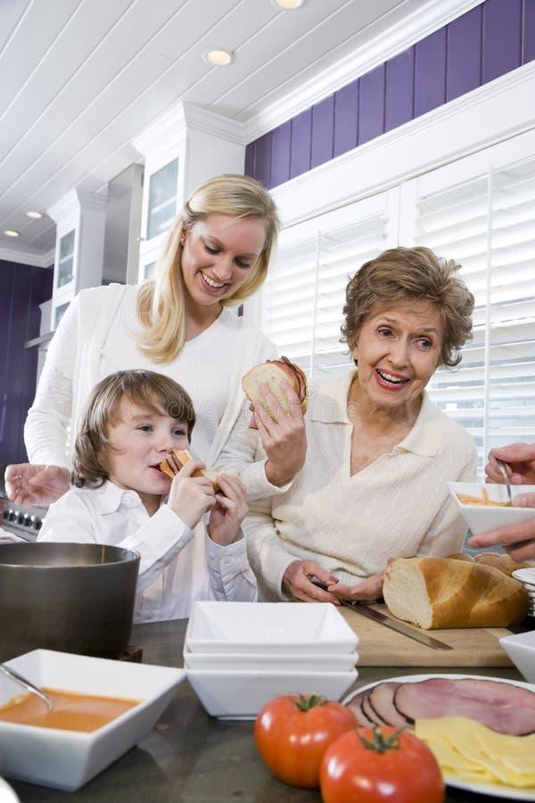 äta familjutvecklingskök äta lunch tre arkivbild