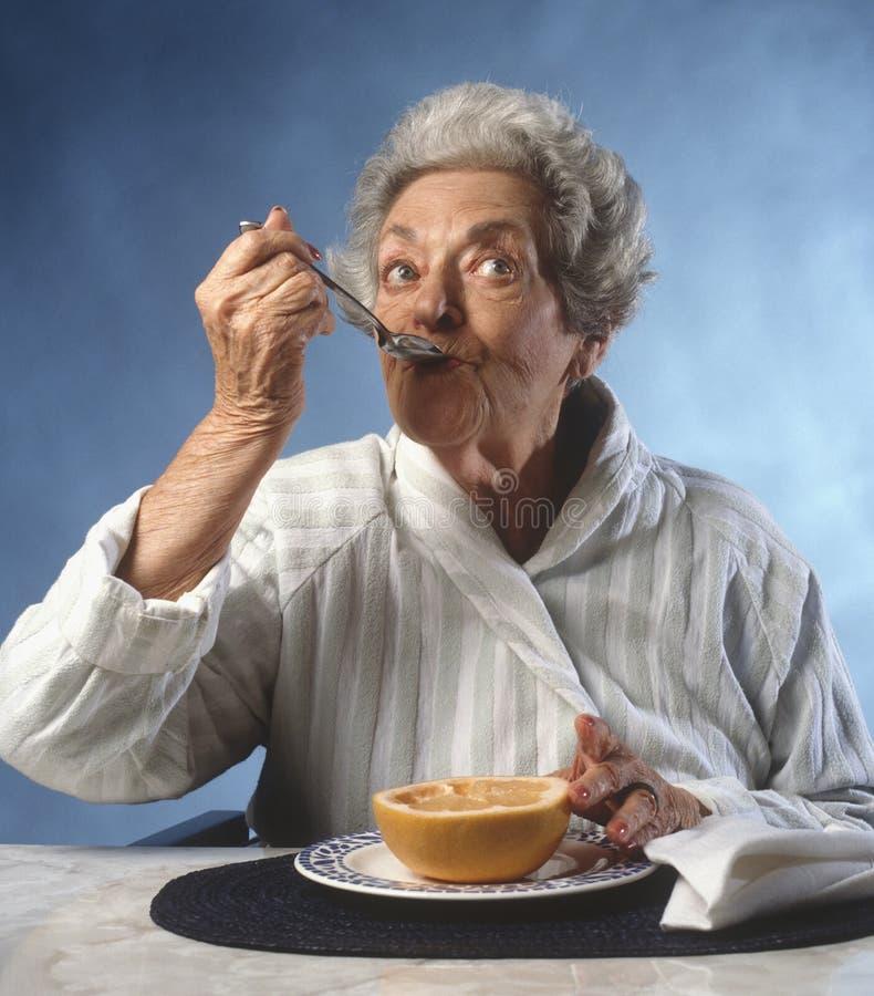 äta grapefruktpensionärkvinnan royaltyfri fotografi
