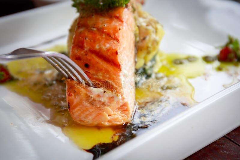 Äta grillade Salmon Steaks med limefrukt och bakade spenat royaltyfria foton